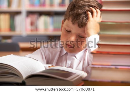 Image of interested schoolkid reading book in the library - stock photo