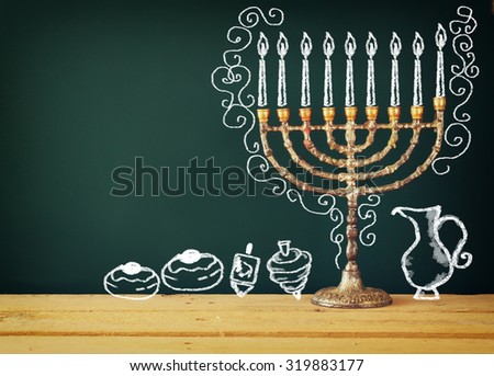 image of jewish holiday Hanukkah with drawing menorah candles (traditional Candelabra), donuts and dreidels (spinning top) over chalkboard background   - stock photo