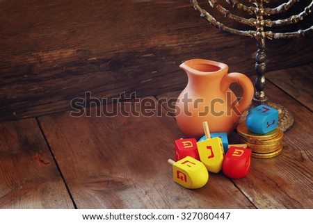 image of jewish holiday Hanukkah with menorah (traditional Candelabra) and wooden dreidels (spinning top)   - stock photo