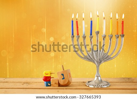 image of jewish holiday Hanukkah with menorah (traditional Candelabra) and wooden dreidels (spinning top). glitter background  - stock photo
