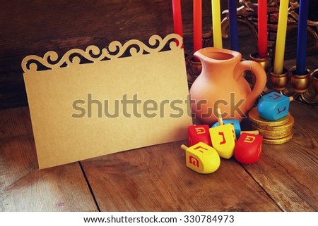 image of jewish holiday Hanukkah with menorah (traditional Candelabra) and wooden dreidels (spinning top) with empty card for adding text  - stock photo