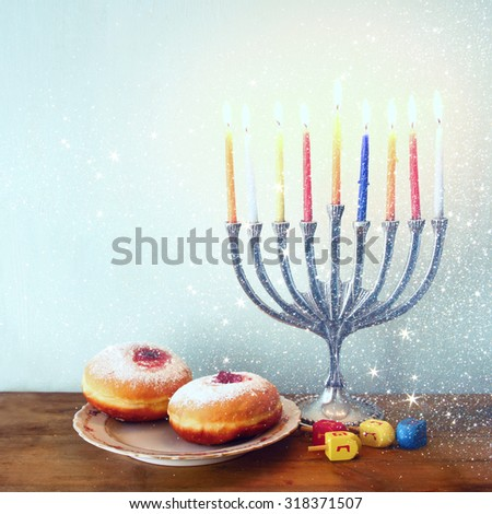 image of jewish holiday Hanukkah with menorah (traditional Candelabra), donuts and wooden dreidels (spinning top). retro filtered image with glitter overlay - stock photo