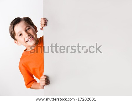 Image of laughing lad looking from behind white vertical partition - stock photo