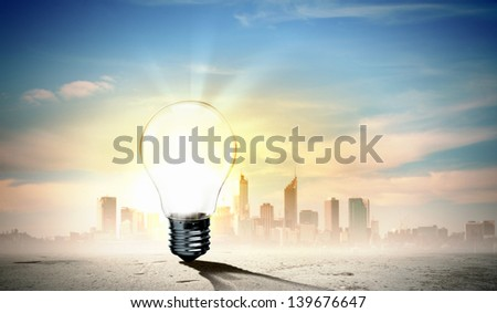 Image of light bulb against city background. Ecological concept - stock photo
