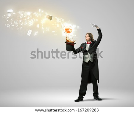 Image of magician with hat and computer devices flying in air - stock photo