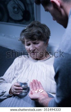Image of male carer and elderly woman taking medicines - stock photo