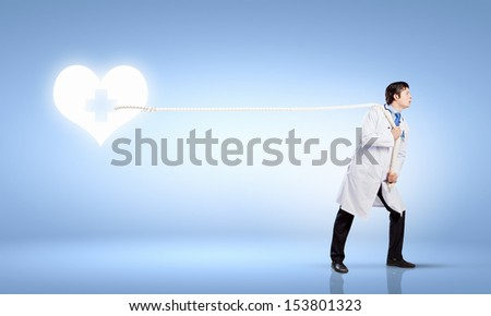 Image of male doctor pulling health sign with rope - stock photo
