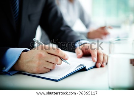 Image of male hand with pen over open notebook at seminar - stock photo