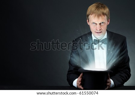 Image of male magician holding hat with magic light and looking at camera - stock photo