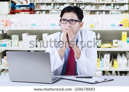 Image of male pharmacist thinking something in the drugstore with laptop on the table - stock photo