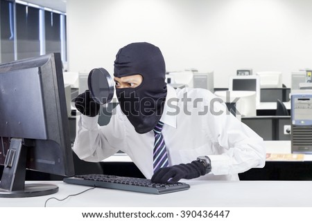 Image of male thief using magnifier and wearing mask to steal information on the computer at workplace - stock photo