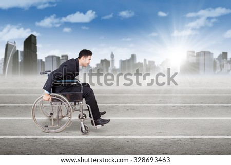 Image of male worker with format suit and sitting on the wheelchair, pushing the wheelchair on the race line - stock photo