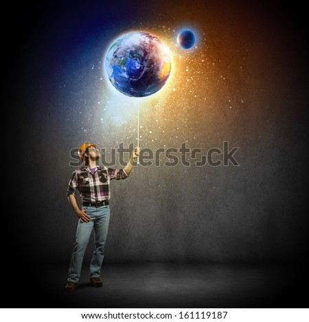 Image of man builder looking at planet Earth. Elements of this image are furnished by NASA - stock photo