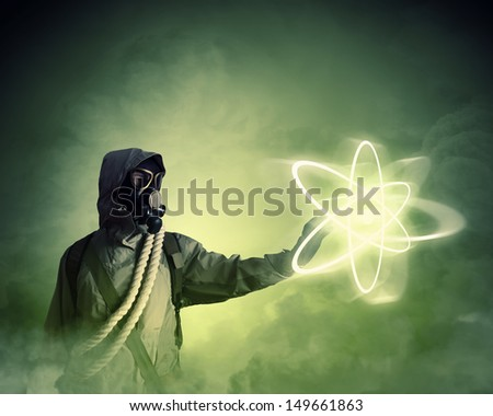 Image of man in gas mask and protective uniform touching atom sign - stock photo