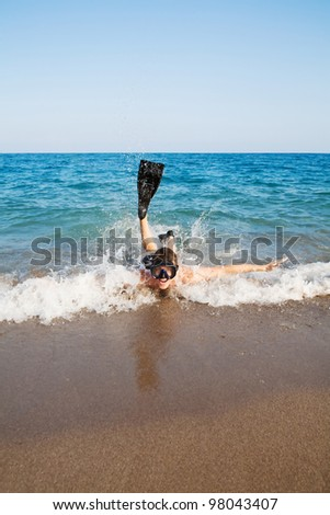 Image of man in goggles and flippers lying in the sea and doing splashing - stock photo