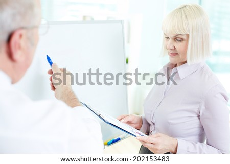 Image of mature businesswoman listening to her partner making presentation on whiteboard at meeting - stock photo