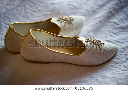 Image of men's Indian wedding shoes on a bed - stock photo