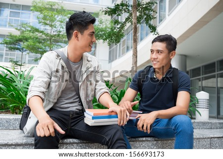 Image of modern young student sitting with books and talking outside - stock photo