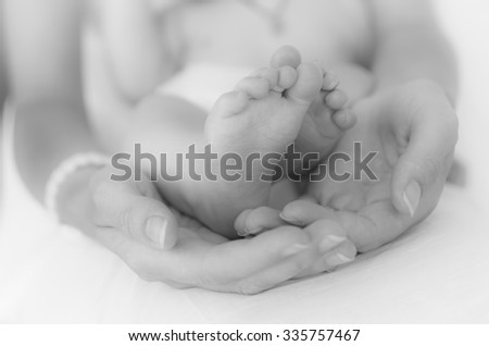 Image of mother's hands and baby's legs - stock photo