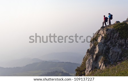 Image of mountain scenery, on top of which stands the silhouette of a tourist couple, who enjoys success achieved heavy climbing. - stock photo