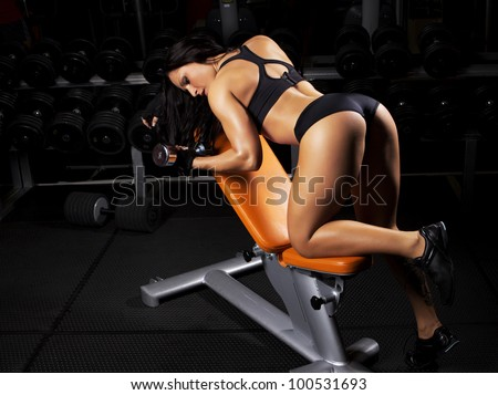 Image of muscle woman doing exercises in gym - stock photo