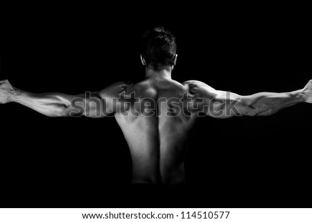 Image of muscular man posing in studio black and white - stock photo