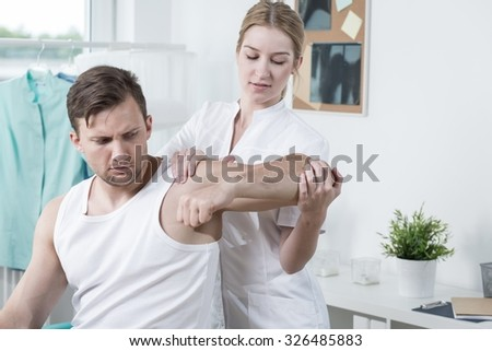 Image of muscular man with hand ache exercising with physiotherapist - stock photo