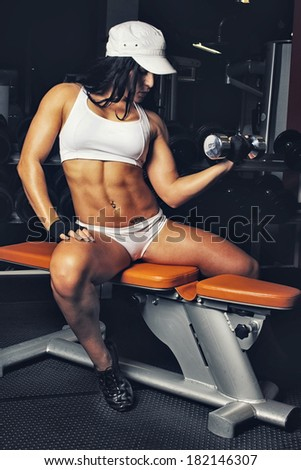 Image of musle woman doing exercises in gym with dumbbels - stock photo