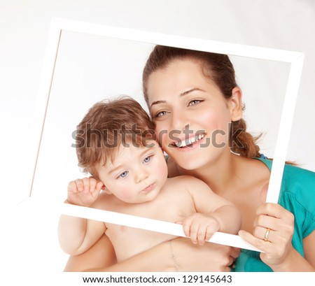 Image of nice mother with lovely son hugging and isolated on white background, beautiful woman with cute toddler holding in hands white frame, happy childhood, love concept - stock photo