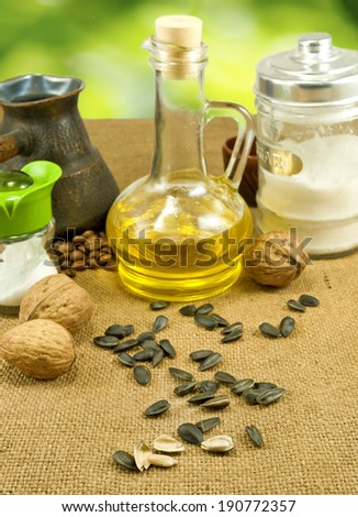 image of  nuts, seeds,butter, salt shaker, coffee beans, a cup on a green background - stock photo