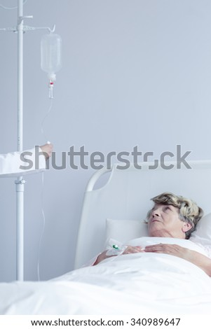 Image of old patient lying with intravenous drip - stock photo