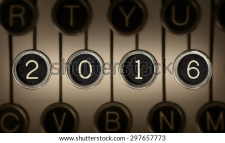 """Image of old typewriter keyboard with scratched chrome keys that form """"2016"""". Lighting and focus are centered on """"2016"""".  - stock photo"""