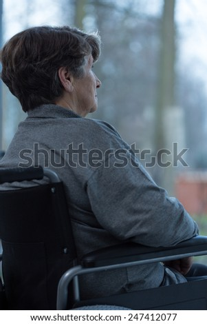Image of older injured woman sitting on a wheelchair - stock photo