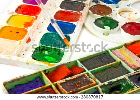 image of paints and brushes on a white background closeup - stock photo