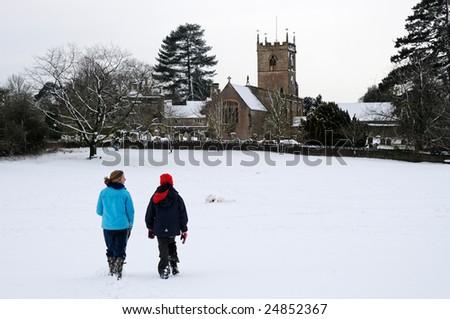 image of people walking towards village church - stock photo