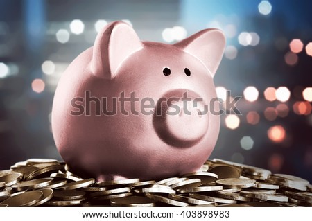 Image of piggy bank on the stop of coins with city background - stock photo