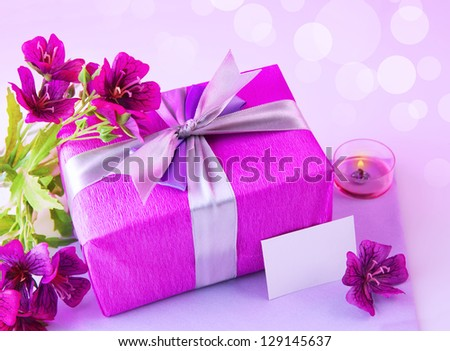 Image of pink giftbox with silk bow, fresh purple flowers, candle and blank postcard isolated on blur background, festive still life, happy mothers day, romantic holiday, love and romance concept - stock photo