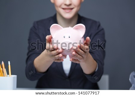 Image of pink piggy bank held by female - stock photo