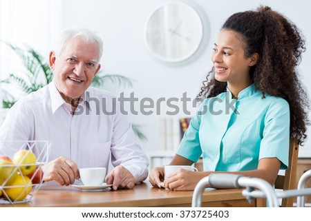 Image of positive afroamerican carer and retired man - stock photo