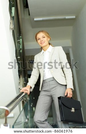 Image of pretty businesswoman with briefcase going down in office building - stock photo