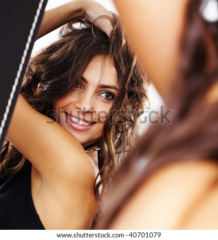 Image of pretty female looking in mirror and enjoying herself - stock photo