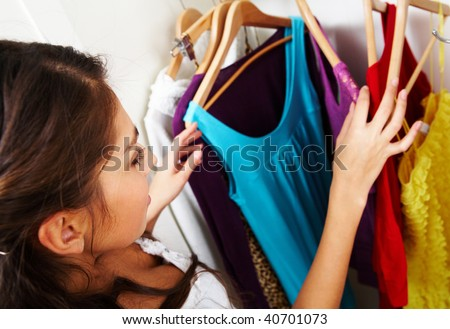 Image of pretty female looking through her wardrobe and choosing smart dress - stock photo