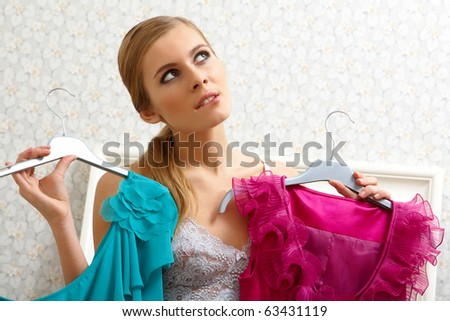 Image of pretty female thinking what dress to wear on New Year night - stock photo