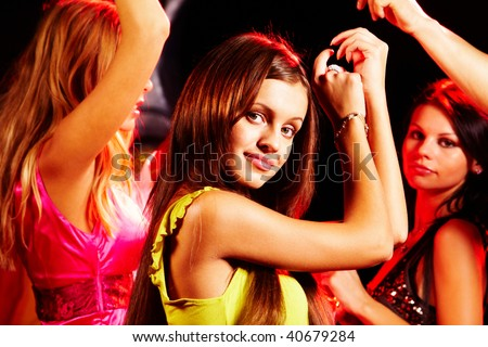 Image of pretty girl looking at camera while dancing on background of her friends - stock photo