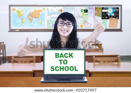 Image of pretty student with a text of back to school on the laptop, showing thumbs up in the classroom - stock photo