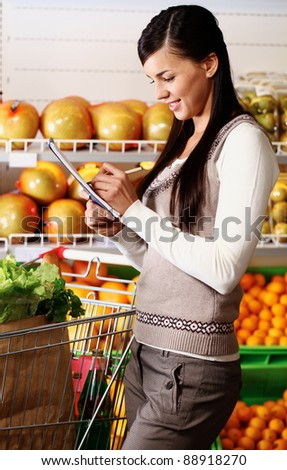 Image of pretty woman ticking what she has bought in supermarket - stock photo