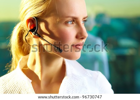 Image of pretty woman with headset looking forward - stock photo