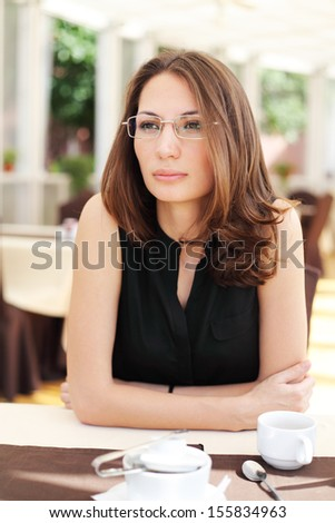 Image of pretty young businesswoman in cafe - stock photo
