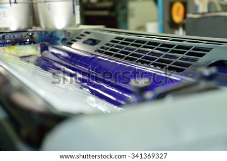 Image of process cyan ink in the fountains and on the rollers of a offset color printing press. - stock photo