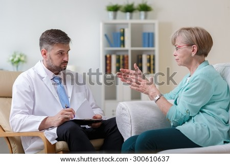 Image of psychiatrist listening to his female patient with depression - stock photo